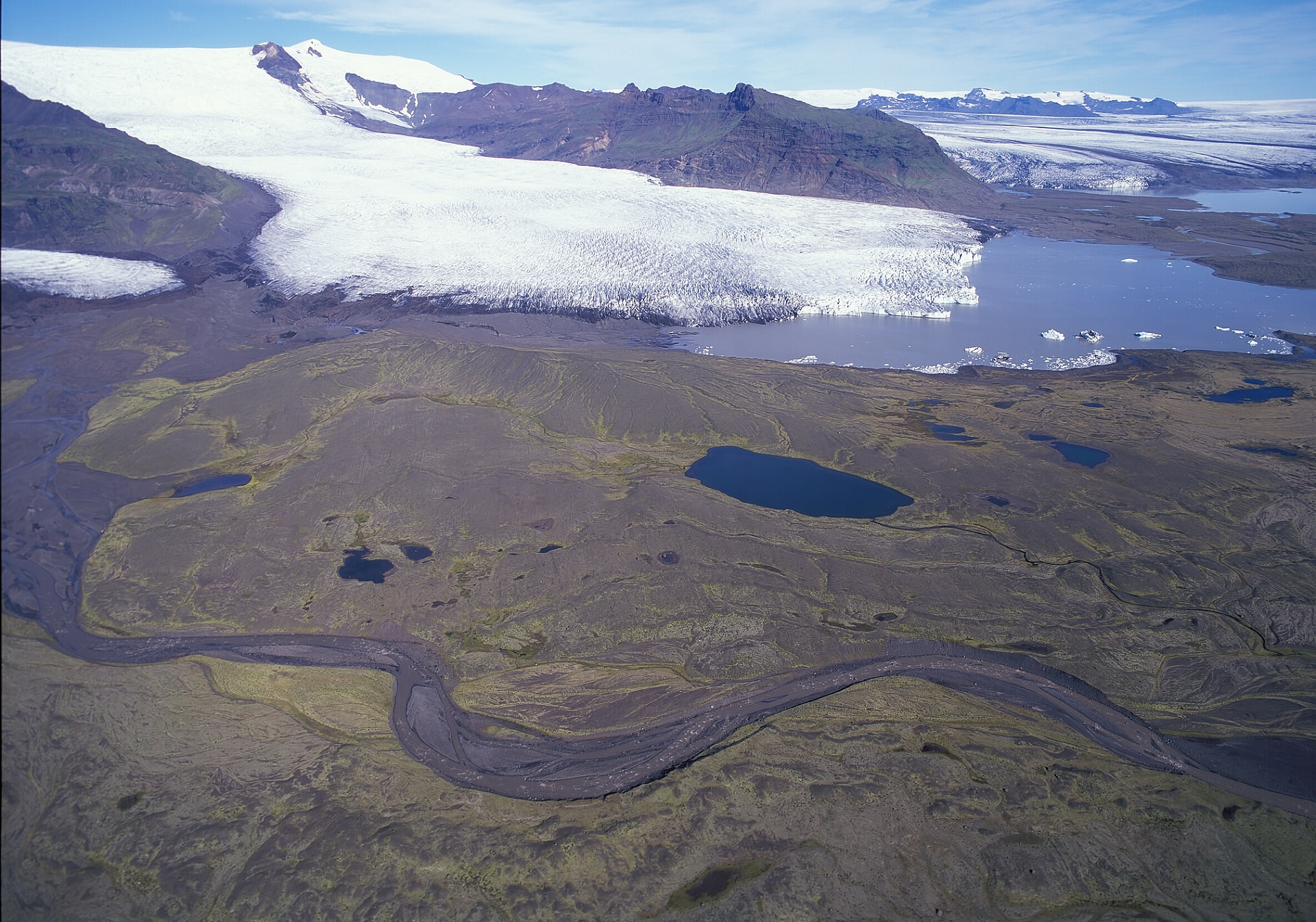 The snout of Hrútárjökull, Fjallsárjökull and Breiðamerkurjökull outlet glaciers in the background. The Little Ice Age moraines from ca 1890 are visible in the moss covered sandur plain. Terminal glacial lakes have increased in size in recent decades and enhance ablation. Photo: Snævarr Guðmundsson, 2006.