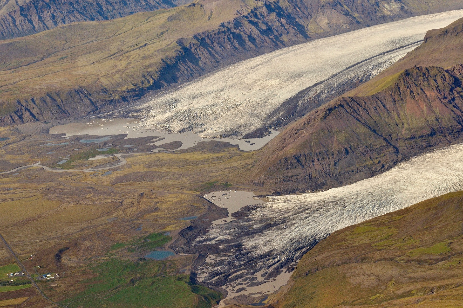 Svínafellsjökull outlet glacier with several small, separate lakes (front) and Skaftafellsjökull outlet glacier with an elongated lagoon between the glacier moraine and the terminus (back). Photo: Snævarr Guðmundsson, September 13th 2014.